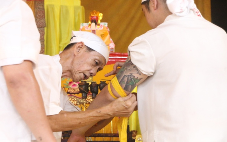 Uncle Ah Huat assisting James in the wearing of the Heavenly Generals.
