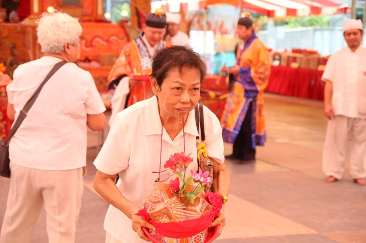 Devotees and members of the temple bowing together with the offerings during the Xian Gong (献贡) ritual. The offerings include lanterns, flowers as well as their personal belongings.