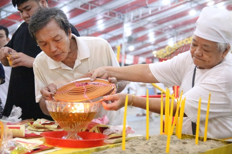 After the Nine Lamps are raised, devotees pay their respect to the Nine Emperor Gods by offering Joss sticks and burning of incense paper.