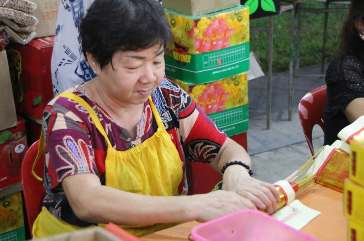 James' mother, Auntie Ah Hong bundling incense paper with joss sticks together for offering purposes.
