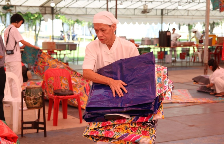 Uncle Ah Huat folding the paper clothing donated by devotees for the Song Tian Gong (送天宫) ritual.